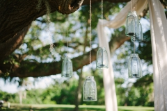 Kerzengläser-und-weißer-Stoff-in-Baum-hängend-M