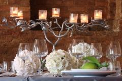 Tischdekoration-weiße-Rosenkugeln-vor-Backsteinwand-+-großer-Leuchter-M