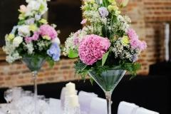 hohe-bunte-Blumengestecke-auf-langer-Tafel-M