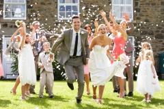Brautpaar-strahlend-mit-Gästen-+-fliegende-Rosenblätter-M