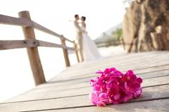 Brautstrauß-pink-auf-Holzsteg-im-Hintergrund-Brautpaar-M